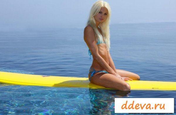 Голая блондинка катается на серфинге