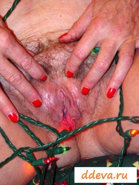 Обмотанная гирляндами обнаженная старушка